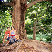 Young hiking couple sitting on exposed roots of old tree