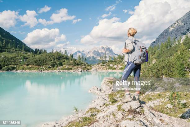 Young hiking woman contemplating Alpine lake in Italy, Dolomites