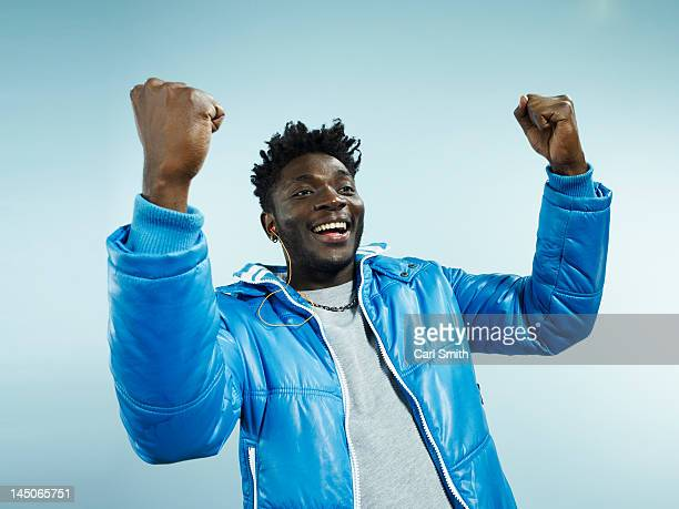 A young hip man with his arms raised in celebration