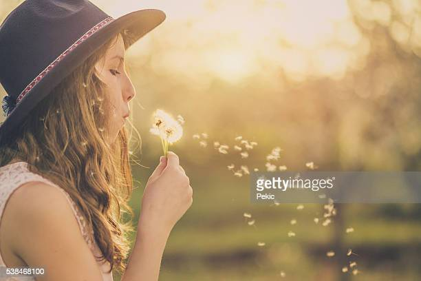 Young hippie girl blowing dandelion outside