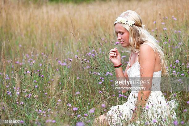 young hippie girl smelling nature field flower