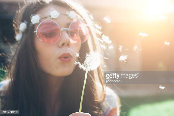 Young hippie woman blowing dandelion outside