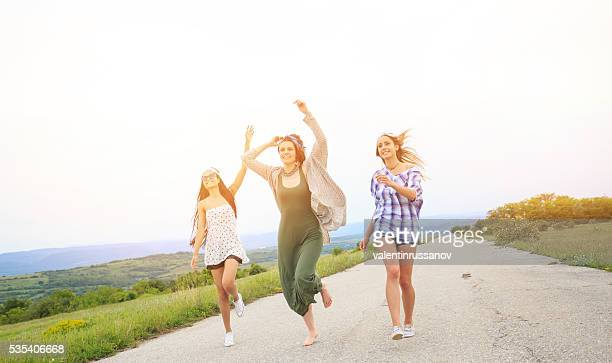 Young hippie women jumping and having fun on the road