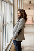 Young hipster businessman looking out of window