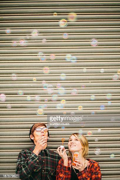 Young Hipster Couple Blowing Bubbles