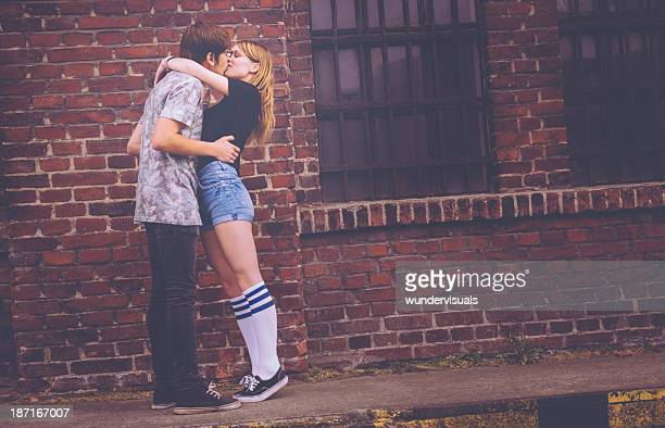 Young Hipster Couple Kissing against grunge building
