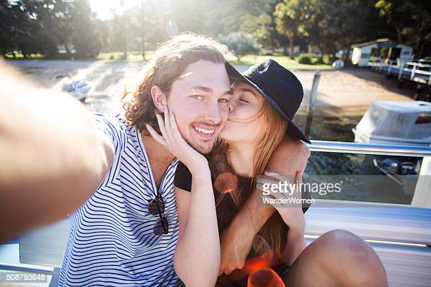 Young hipster couple kissing on boat taking selfie