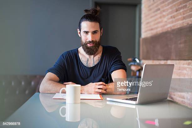 Young hipster designer looking at camera