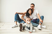 Young hipster father, mother and cute baby boy sitting on rustic wooden floor over white background
