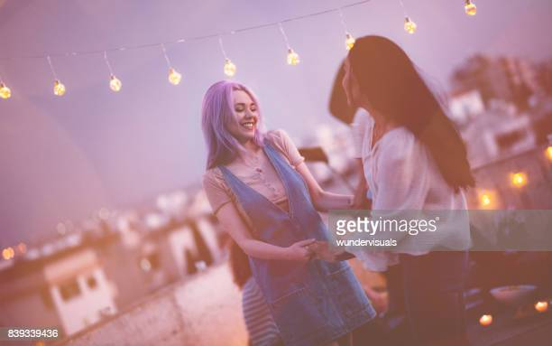 Young hipster female friends dancing at urban rooftop summer party