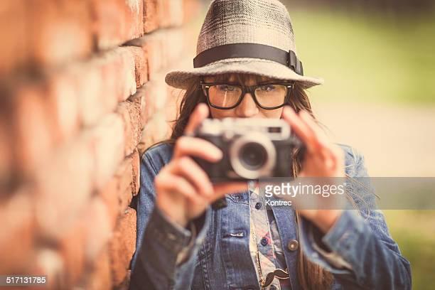 若いヒップスターの少女の写真をビンテージカメラ屋外