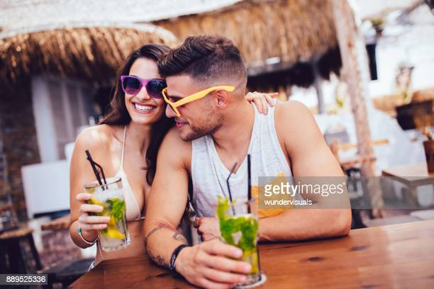 Young hipster man and woman drinking cocktails at summer bar