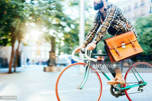 Young hipster man speeding with his bike.