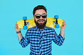 Young hipster bearded man with a yellow skateboard and sunglasses smiling on blue background