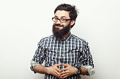 Young hipster man with beard and sunnglasses posing and looking to the camera isolated over white background in studio