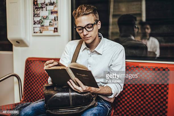 Junge hipster lesen ein Buch auf der U-Bahn