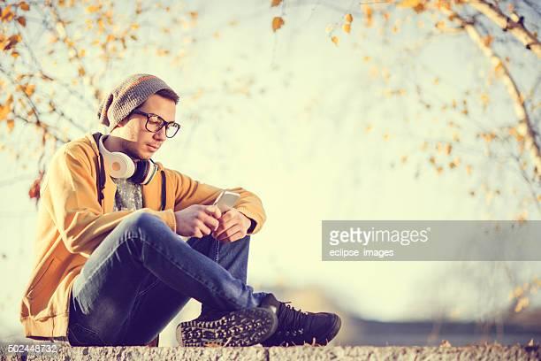 Jeune hipster à l'aide d'un téléphone mobile