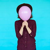 Young hipster woman holding balloon over her face. Pink and turquoise colors fashion concept