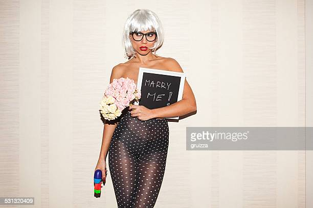 Young hipster woman holding chalkboard that says: Marry me