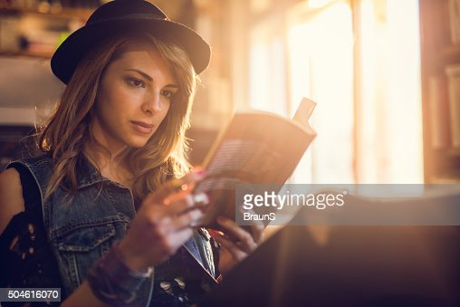 Young hipster woman relaxing while reading a book.