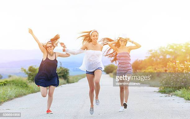 Young hipster women jumping and having fun on the road