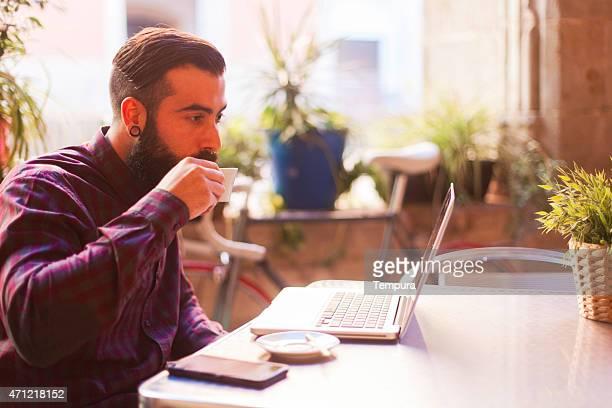 Giovane hipster lavorare in viaggio e bere caffè