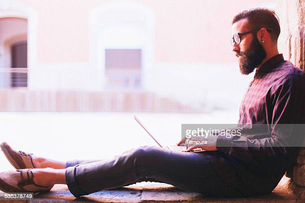 Young hipster working with laptop outdoors.
