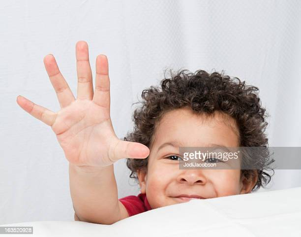 Young hispanic boy counting five fingers