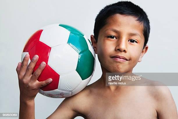 A young Hispanic boy holding a soccer ball