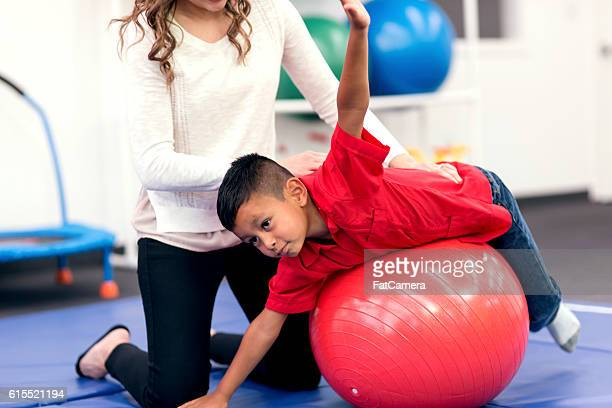 Young hispanic boy using an exercise ball for therapy