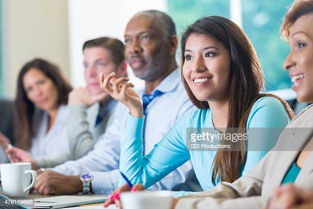 Young Hispanic businesswoman answering question during business seminar conference