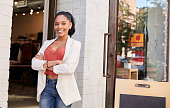 Young Hispanic businesswoman smiling to camera outside her shop