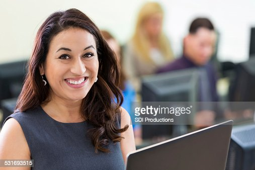 Young Hispanic businesswoman using computer during job training course