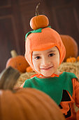 Young Hispanic child in pumpkin costume with pumpkins