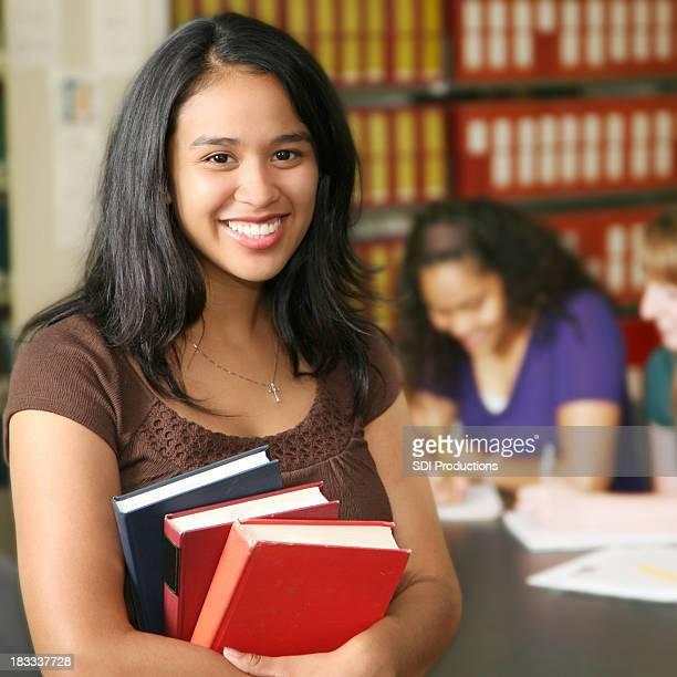 Junge hispanische College Student hält Bücher in Campus Bibliothek