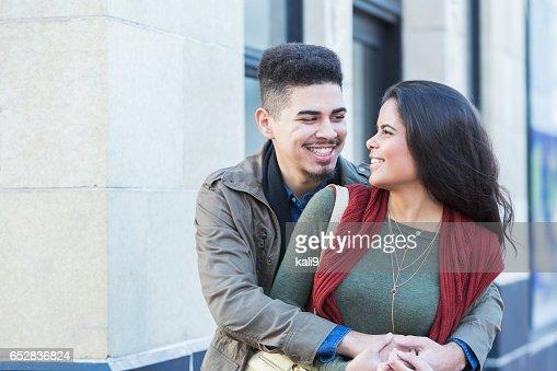 Young Hispanic couple embracing on city sidewalk : Stock-Foto