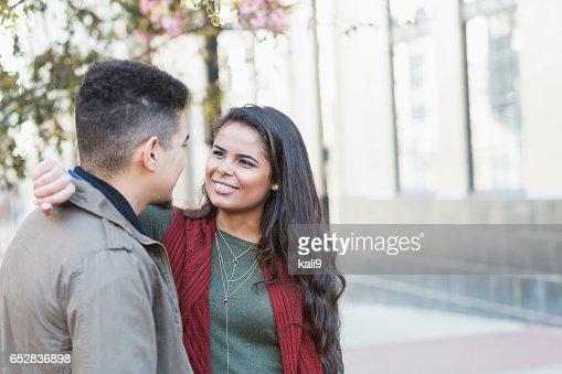 Young Hispanic couple standing on city sidewalk : Stock Photo
