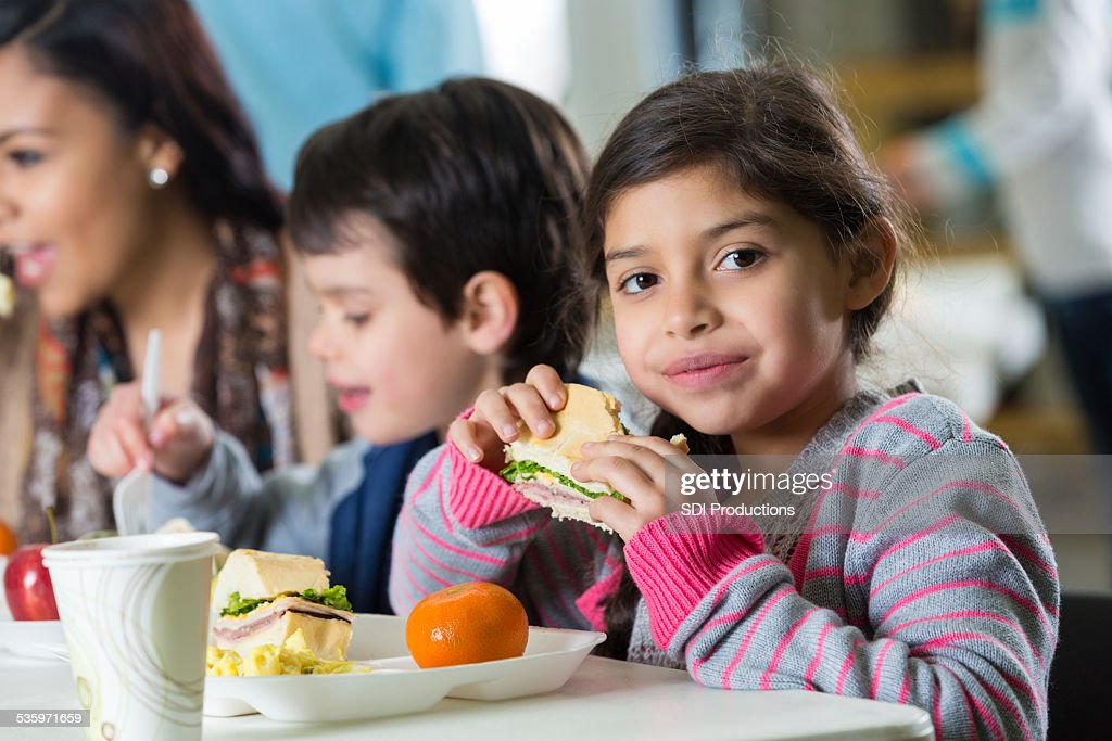 Young Hispanic family eating meal at neighborhood soup kitchen : Stock Photo