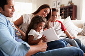Young Hispanic family of four sitting on the sofa reading book together in their living room