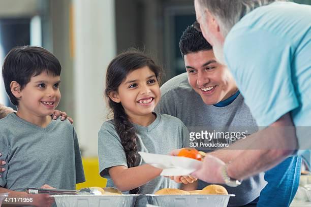 Young Hispanic family ehrenamtliche Tätigkeiten in food bank Küche
