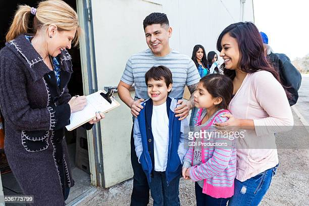 Young Hispanic family waiting in line at food bank
