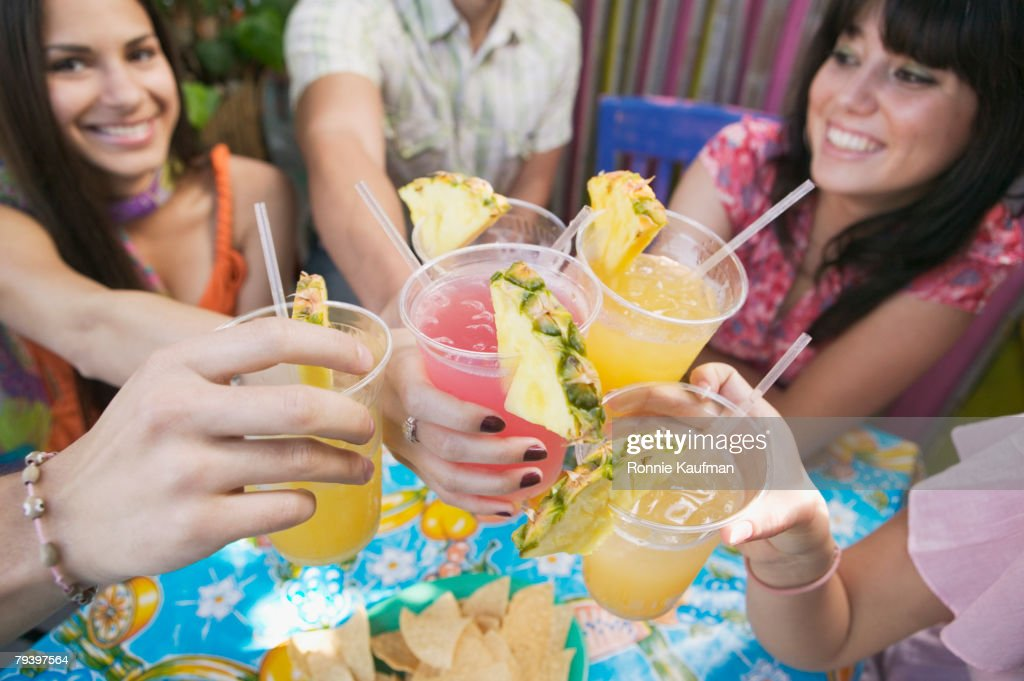 Young Hispanic friends toasting with cocktails : Stock Photo