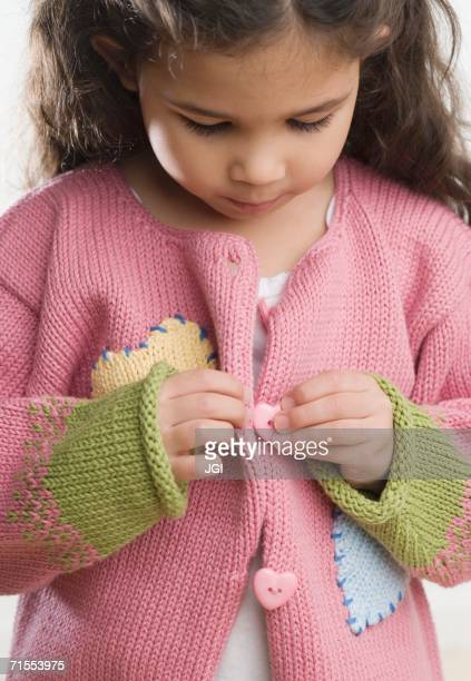 Young Hispanic girl buttoning sweater