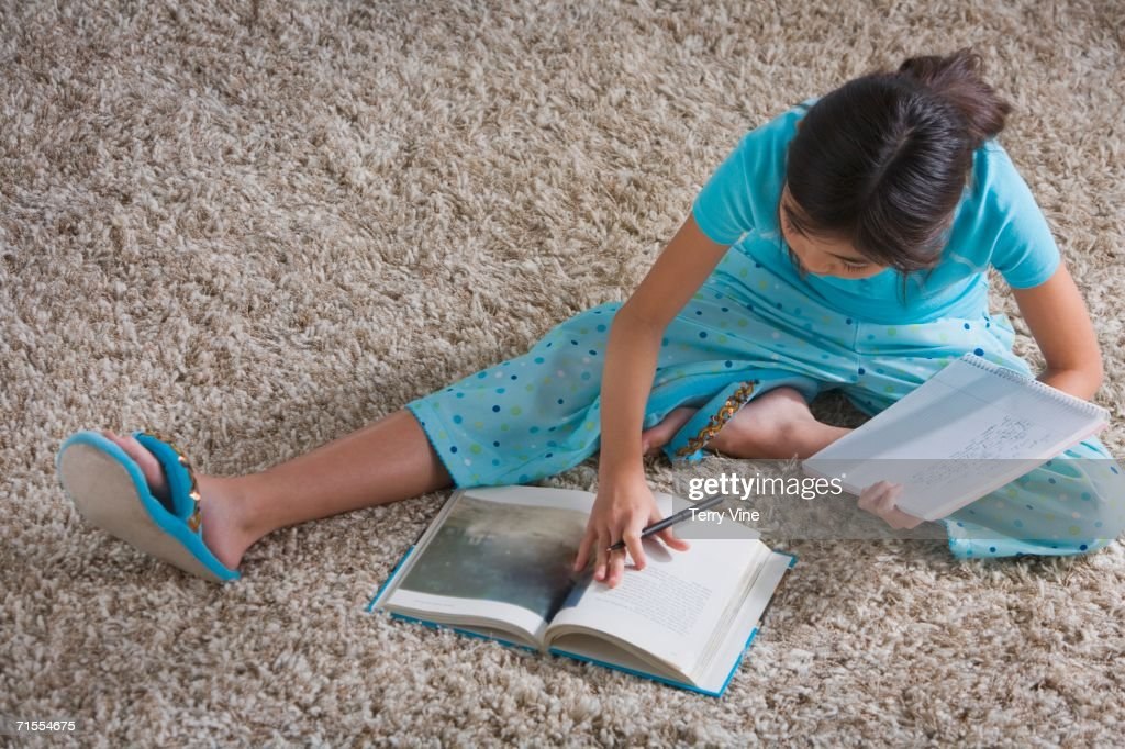 Young Hispanic girl doing homework on the floor : Stock Photo