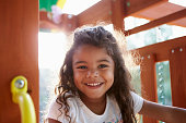 Young Hispanic girl playing on a climbing frame in a playground smiling to camera, backlit, close up
