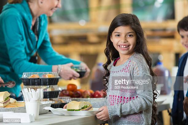 Young Hispanic girl receiving meal at food bank kitchen