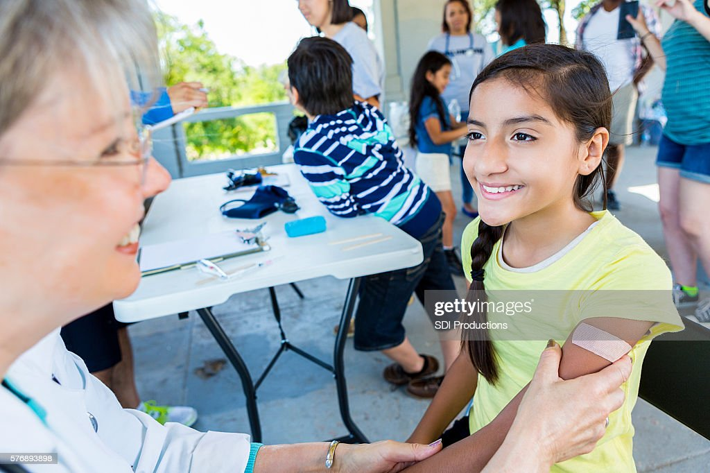 Young hispanic girl smiling at doctor after getting a shot