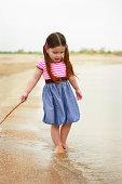 Pretty young Hispanic girl walking along the shore line.