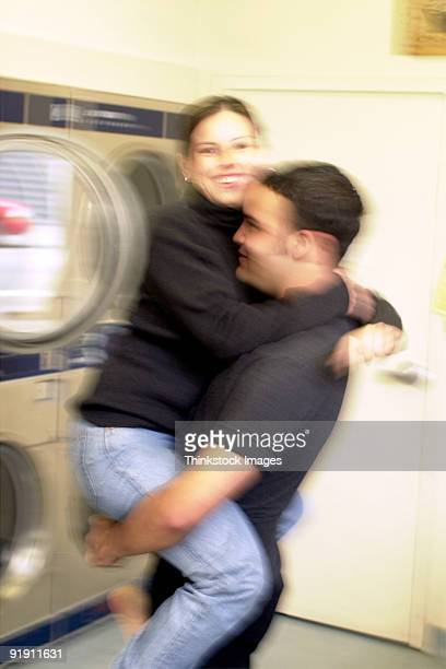Young Hispanic male picking up a young Hispanic female in a laundromat