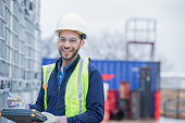 Young adult Hispanic man is chemical engineer, checking inventory of chemical shipment at oil and gas industry job site. Pipeline pipes and other equipment are in background. Man is wearing safety gea